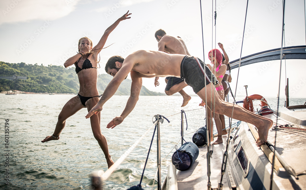 Fototapeta Fiends having fun on a sail boat and jump in the water