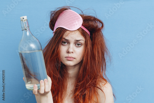 Cuadros en Lienzo Woman with a bottle of alcohol, the morning after a party, a hangover