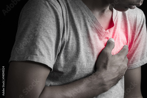 Photo Man clutching his chest from acute pain heart attack symptom.
