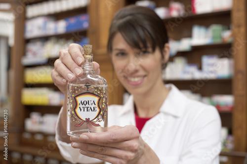 Female pharmacist holding a bottle of Aqua Vitae (aquavit, water of life) at cam Canvas Print