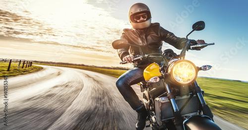 Zdjęcie XXL Motocykl jedzie na otwartej wiejskiej drodze w zachodzie słońca