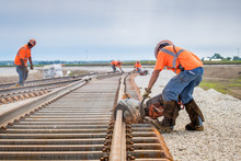 Man Working Rail Saw And Railroad Construction