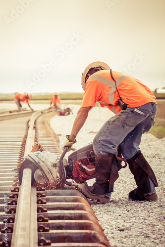 Fotografía  man working rail saw and railroad construction vintage