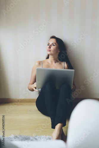 Woman working with laptop while sitting on the floor