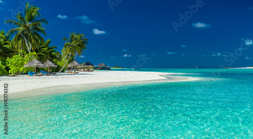 Poster de jardin Plage Palm trees and beach umbrelllas over lagoon and white sandy beach, Maldives