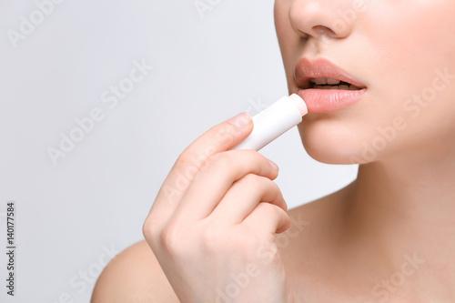 Photographie  Woman applying hygienic lip balm on light background