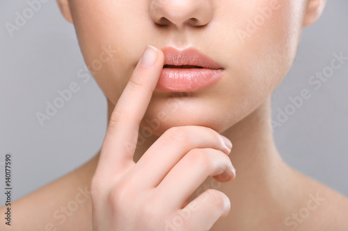 Woman with cold sore touching lips on light background Fototapeta