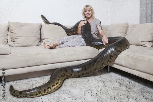 Fényképezés  Frau mit riesiger Anakonda im Wohnzimmer