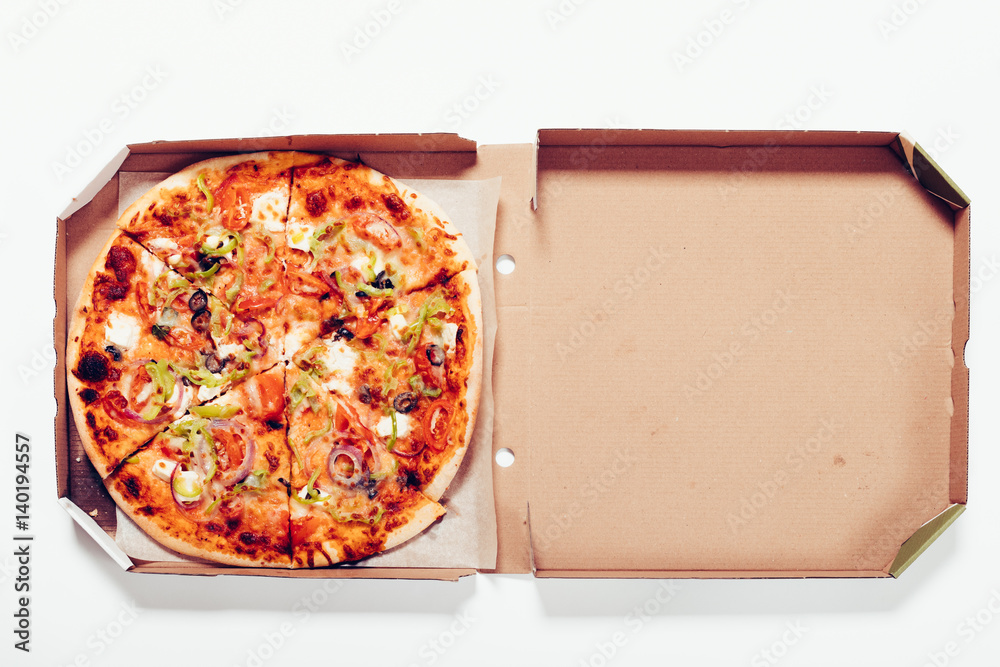 Top view of a pizza in a box on a white table