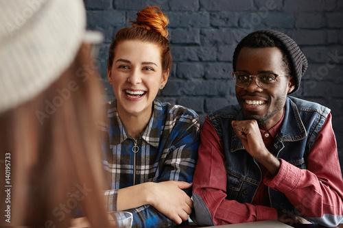 Photo  Group of three happy students having fun indoors: beautiful girl with orange hai