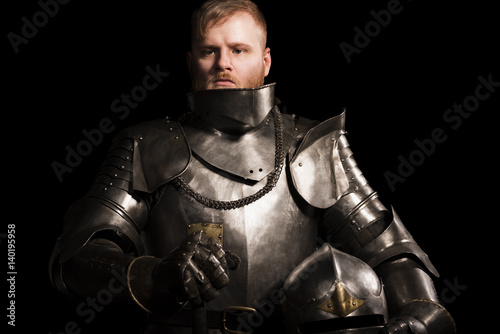 Knight in armour after battle on the black background Wallpaper Mural
