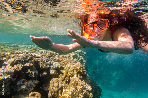Girl in swimming mask dive in Red sea near coral reef