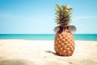 Hipster pineapple with sunglasses on a sandy at tropical beach. concept of fashion in summer. vintage colortone filter effect