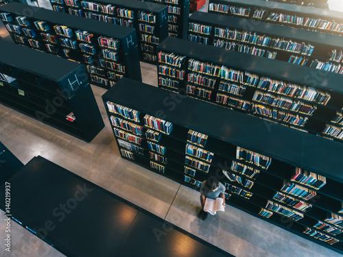 Female student at library bookshelf reading book Fototapeta
