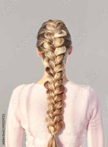 Fotografie, Tablou  Young beautiful woman with nice braid hairstyle on light background