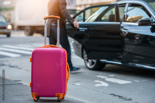 Photographie People taking taxi from an airport and loading carry-on luggage bag to the car