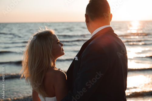 Fototapety, obrazy: Just Married. Beautiful young couple on the beach at sunset