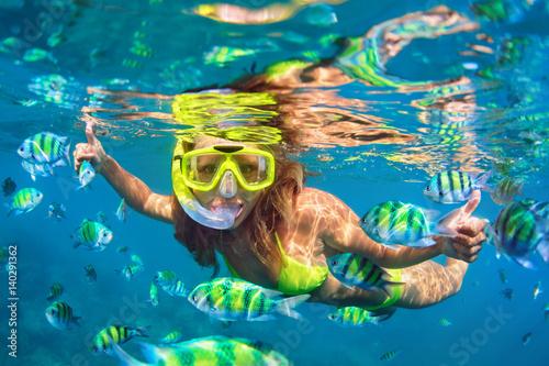 Plakat Szczęśliwa rodzina - dziewczyna w snorkeling maska nurkować pod wodą z ryby szkoły w basenie Morza rafy koralowej. Styl życia w podróży, przygoda na świeżym powietrzu w sportach wodnych, nauka pływania na letnich wakacjach na plaży z dzieckiem.