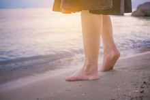 Toe Foot Touches The Sea On The Beach At The Time Of Sunset . Young Business Woman Relaxing Are Happy At Work Concept .