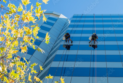 Two window washers abseiling down glass skyscraper Wallpaper Mural