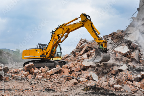 Excavator working at the demolition of an old industrial buildin Canvas Print