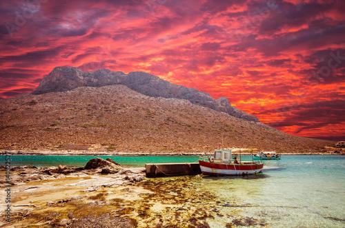 Foto op Plexiglas Crimson Stavros beach on Crete island, Greece. Fishing boat at sunset in Stavros bay.