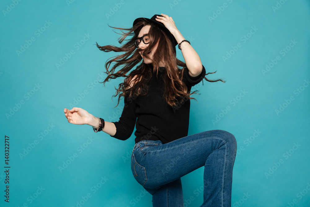 Fototapety, obrazy: Pretty modern young woman in black hat dancing and whirling