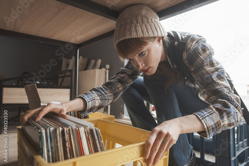Spoed Foto op Canvas Muziekwinkel beautiful young woman audiophille is browsing a crate of second hand records
