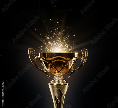 Foto Champion golden trophy on black background