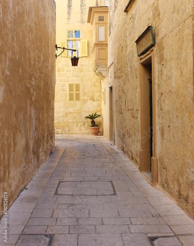 Narrow street with a lantern in old town Mdina, Malta