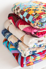 Magnificent Colored Patchwork Quilt Put By A Pile On A White Table Close Up. A Concept With Colorful Scrappy Blankets.