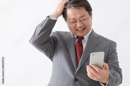 携帯電話を持つビジネスマン 頭をかく 頭を抱える 困る 中年男性 Foto Stock Adobe Stock
