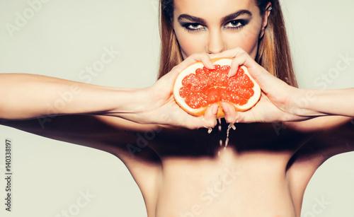 Pretty girl squeezing juice from fresh orange grapefruit