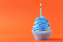 Tasty Cupcake With Candle On Orange Background