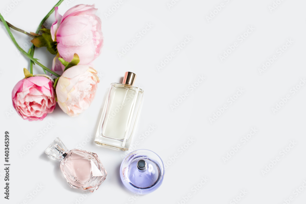 Fototapety, obrazy: Perfume bottles with flowers on light background. Perfumery, cosmetics, fragrance collection. Free space for text.