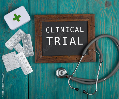 "Fotografia  Blackboard with text ""Clinical trial"", pills and stethoscope on blue wooden back"