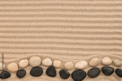 Foto auf Leinwand Zen-Steine in den Sand Two rows of stones lying on the wavy sand, with space for text.