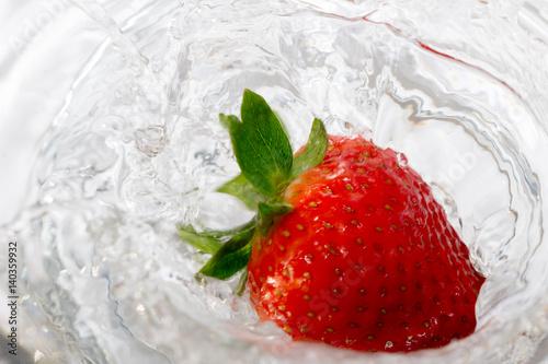 truskawka-wpadajaca-do-wody-w-zblizeniu-widok-z-gory