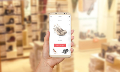 Woman buy shoes online with modern mobile app. Shoe store in background.
