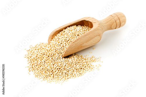 Raw, whole, unprocessed quinoa seed in wooden scoop on white