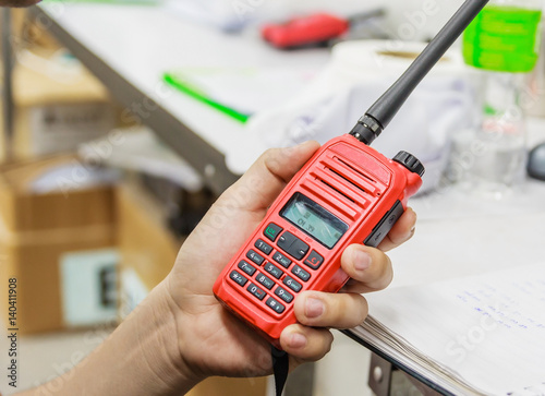 Handheld walkie talkie communication radio for communications at construction site with copy space and text Fototapeta