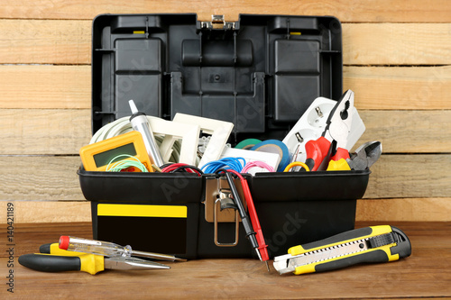 Box with electrician tools on wooden background Canvas Print