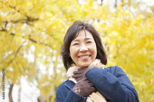 Mature Woman Walking In the Woods In Autumn