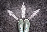Shoes and arrows pointing in different directions on asphalt floor, choice in life for young people concept