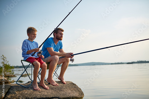 Poster Peche Portrait of handsome bearded father fishing with son sitting on rock in still lake with fishing rods and gear on sunny summer day