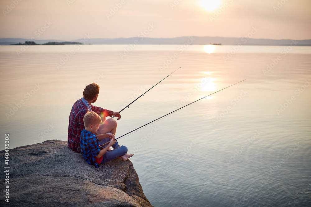 Fototapeta Back view portrait of father and son sitting together on rocks fishing with rods in calm lake waters with landscape of setting sun, both wearing checkered shirts