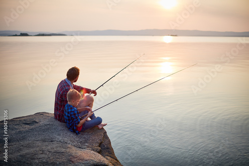Back view portrait of father and son sitting together on rocks fishing with rods in calm lake waters with landscape of setting sun, both wearing checkered shirts