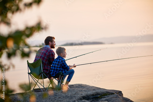 Papiers peints Peche Side view portrait of father and son sitting together on rocks fishing with rods in calm lake waters with landscape of setting sun, both wearing checkered shirts, shot from behind tree