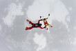 Two skydivers are training in the winter sky.