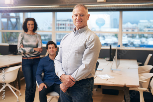 Fototapety, obrazy: Smiling mature manager in an office with colleagues behind him